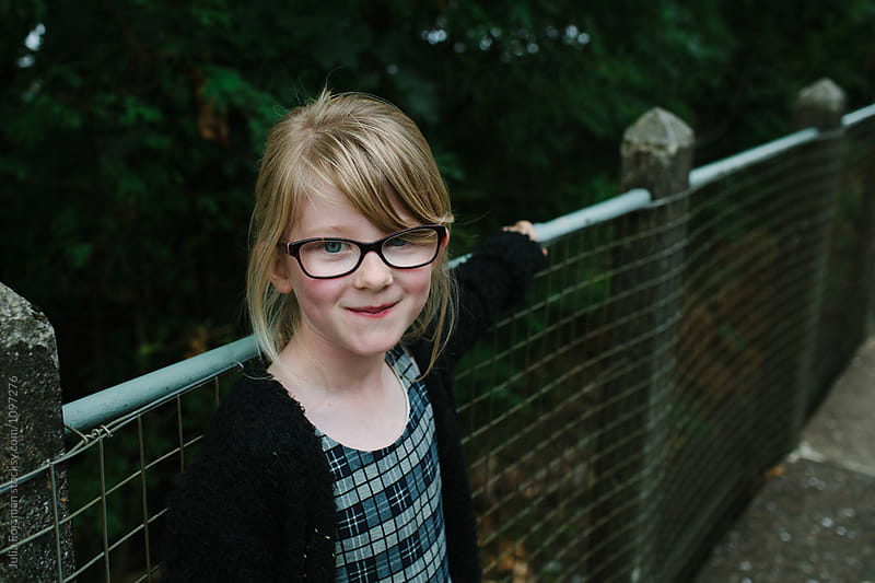 A cheeky girl wearing glasses looks at the camera while waiting outside. by Julia Forsman for Stocksy United