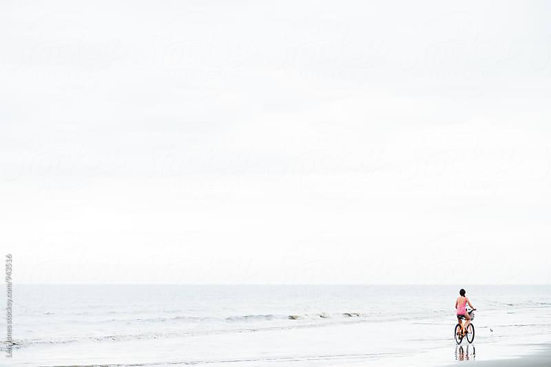 girl biking on the beach by Léa Jones for Stocksy United