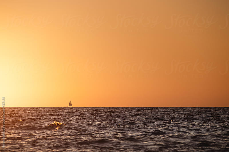 A Small Sailboat Against the Sky at Sunset by Helen Sotiriadis for Stocksy United