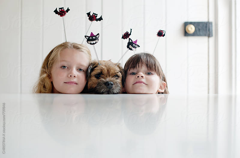 Sisters and their dog peeping over the table by CHRISTINA K for Stocksy United