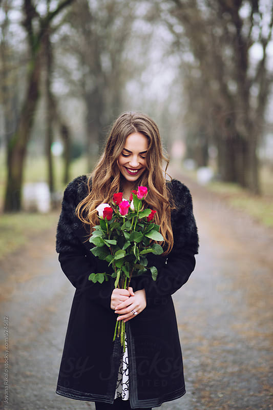 Beautiful young woman holding a bouquet of flowers and smiling by Jovana Rikalo for Stocksy United
