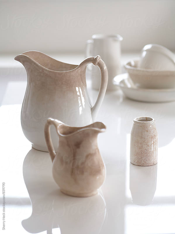 Beige, glazed ceramic pitchers and other vessels on reflective white surface by Sherry Heck for Stocksy United