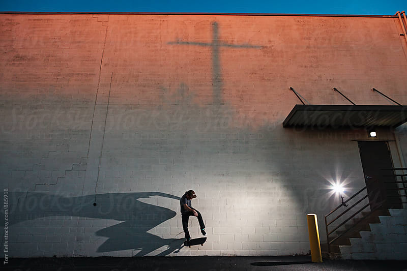 Skateboarder skating and casting shadow in the city at sunset by Tom Eells for Stocksy United
