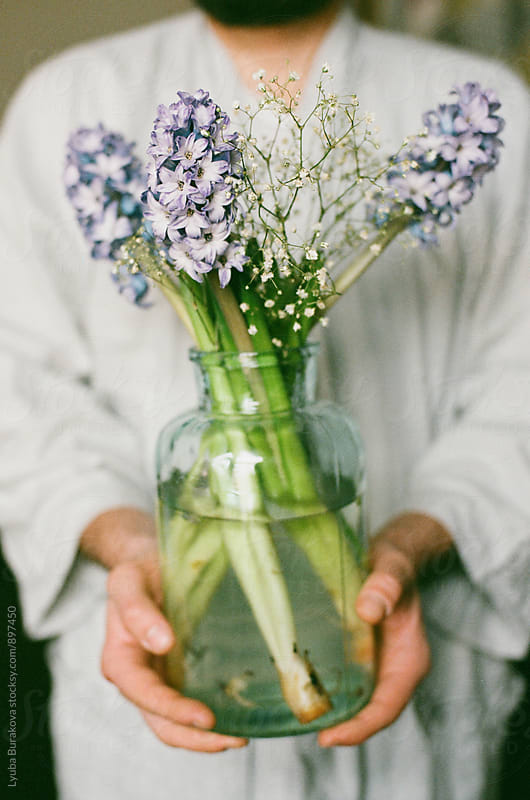 Man holding glass jar with hyacinth by Lyuba Burakova for Stocksy United