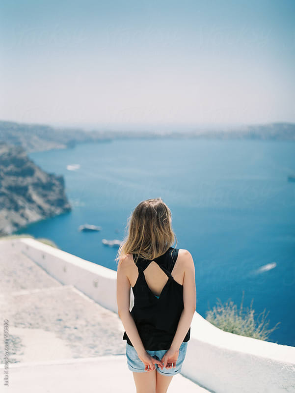 Woman enjoying landscape of Santorini, Greece by Julia K for Stocksy United