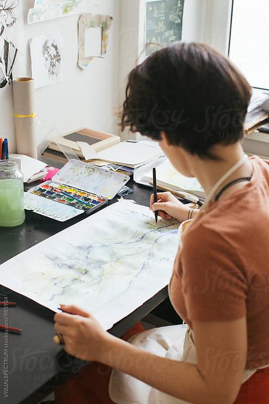 Art Studio - Young Female Brunette Painter Sitting on Desk and Using Art Pen by VISUALSPECTRUM for Stocksy United