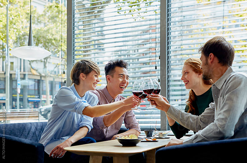 Happy Friends Toasting Wine Glasses In Restaurant by ALTO IMAGES for Stocksy United