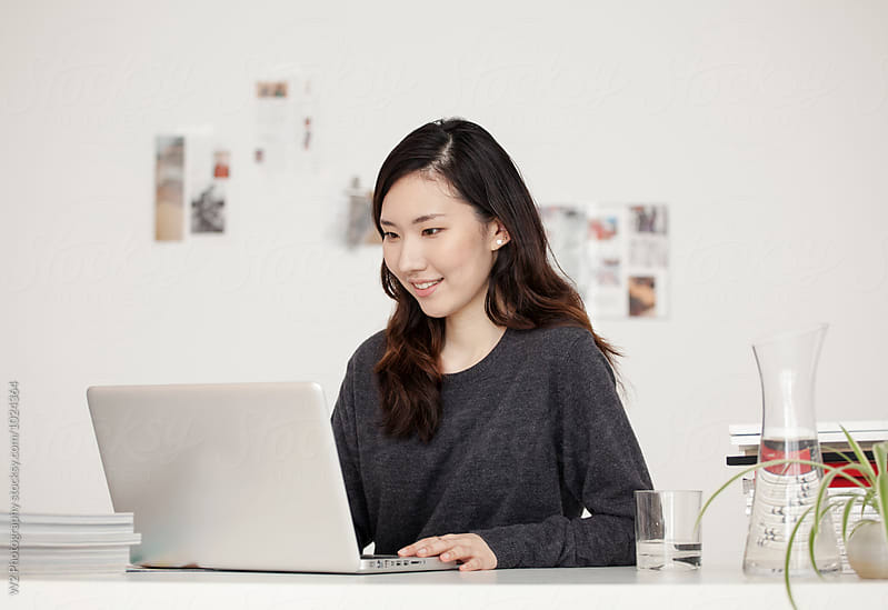 Young woman working at her desk. by W2 Photography for Stocksy United