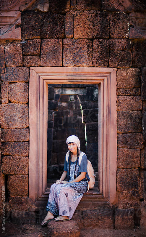 Young woman sitting at the door in the temple area in Siem Reap (Cambodia) by Nabi Tang for Stocksy United