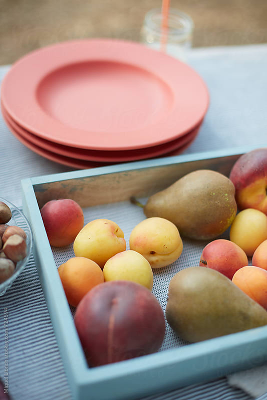 Close up of a tray with colorful fruit on a party table by Miquel Llonch for Stocksy United