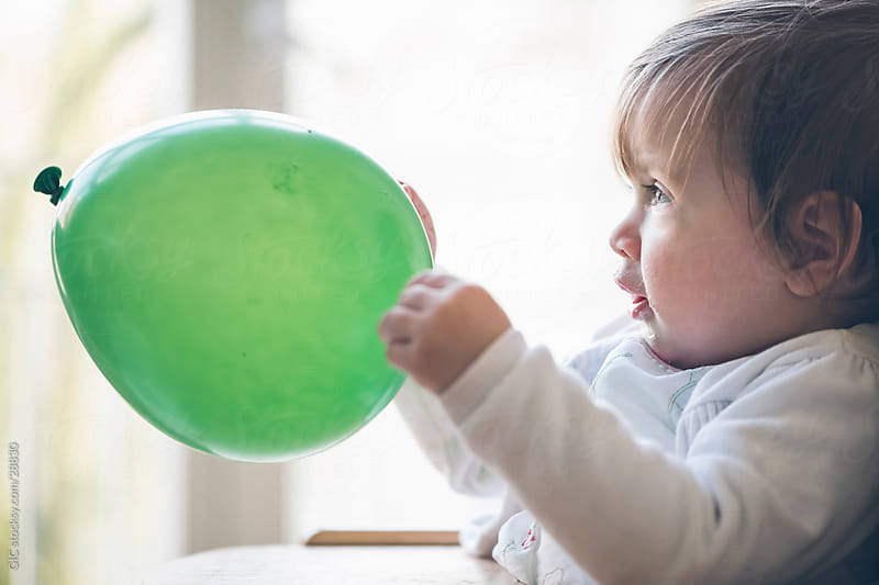 Baby playing with a balloon by GIC for Stocksy United
