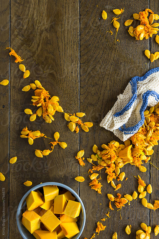 Cleaning up pumpkin seeds and pulp with handmade knitted dishcloth by Kirsty Begg for Stocksy United