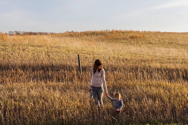 Mother and daughter walking together on prairie farm by Carey Shaw for Stocksy United