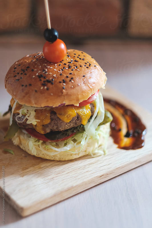 Close up of Beef Burger on the Wooden Board by Branislav Jovanovic for Stocksy United