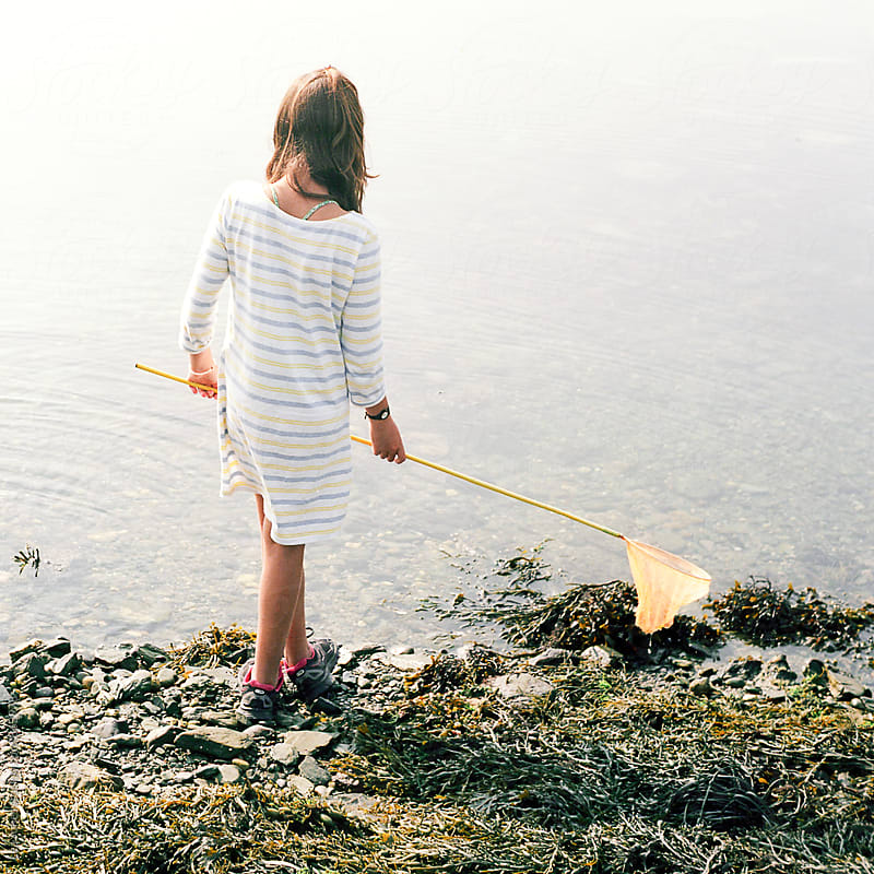 young girl holding  an orange fishing net by Léa Jones for Stocksy United