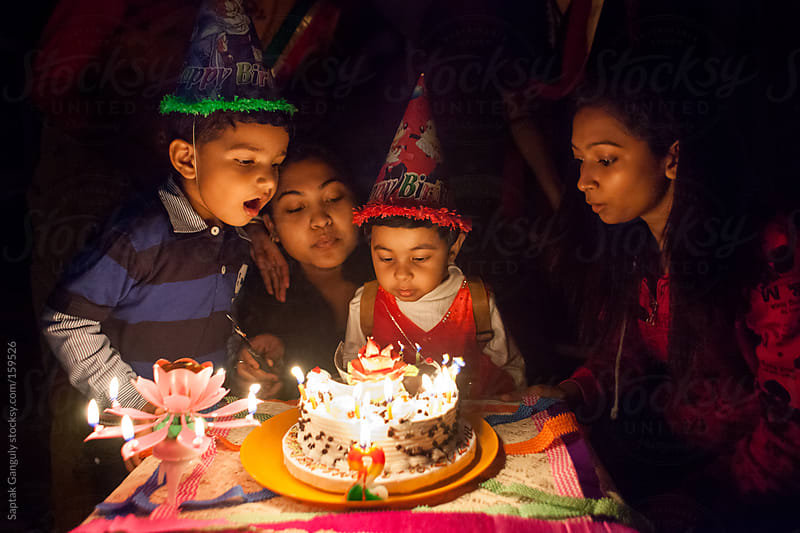 Toddler blowing out candles on her birthday cake by Saptak Ganguly for Stocksy United