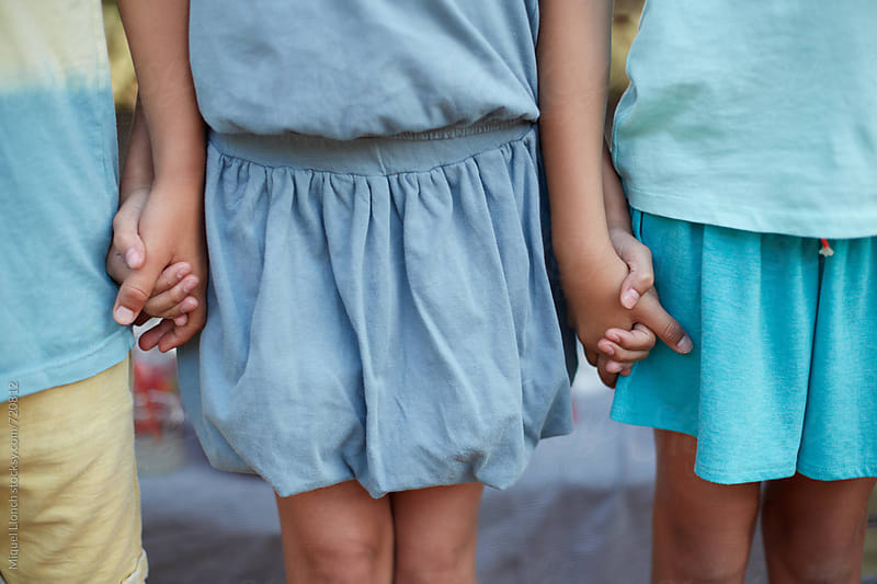 Close up of children holding hands by Miquel Llonch for Stocksy United