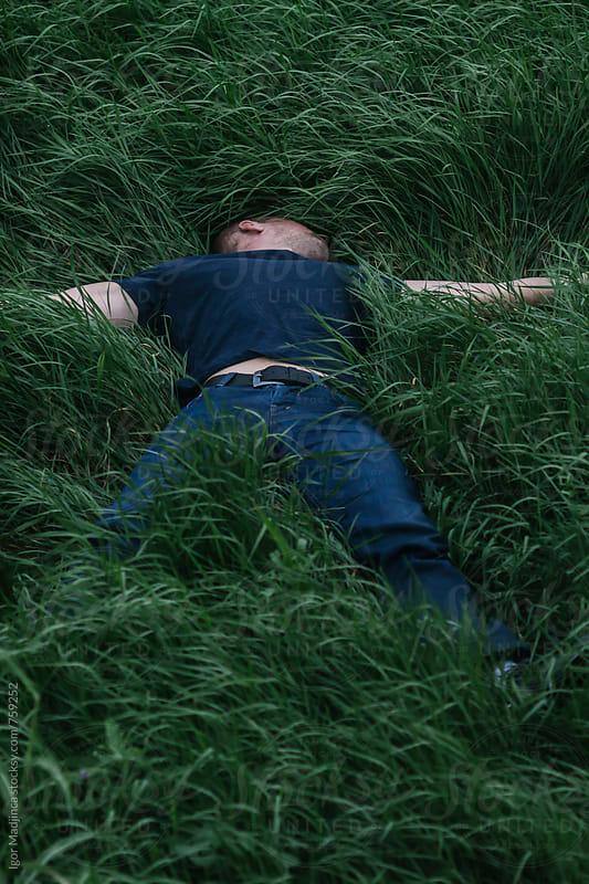 A man dressed in blue lies in the fresh green grass by Igor Madjinca for Stocksy United