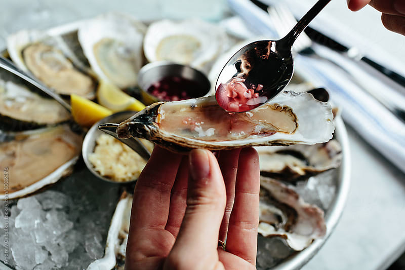 Oysters ready to be consumed at a raw bar by Andrew Cebulka for Stocksy United