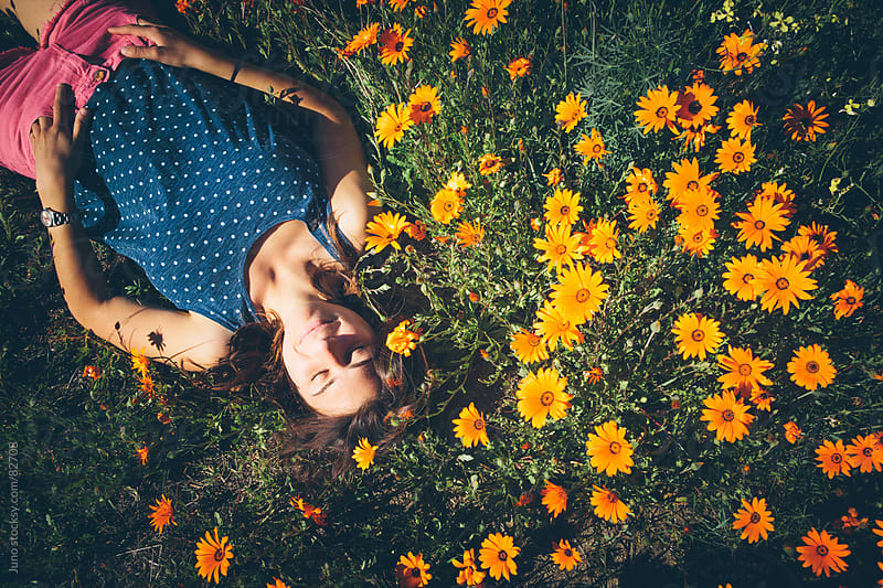 Attractive woman daydreaming in a field of flowers by Micky Wiswedel for Stocksy United