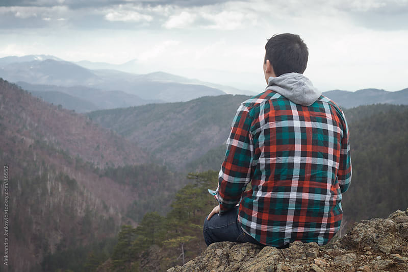 Man sitting on the rock and enjoying the mountain view by Aleksandra Jankovic for Stocksy United