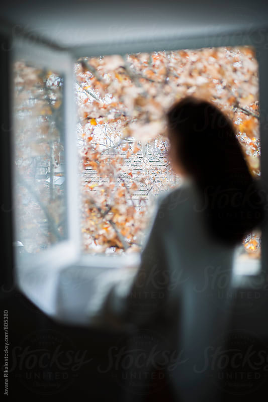 Back view of  a young woman looking through the window ; out of focus by Jovana Rikalo for Stocksy United