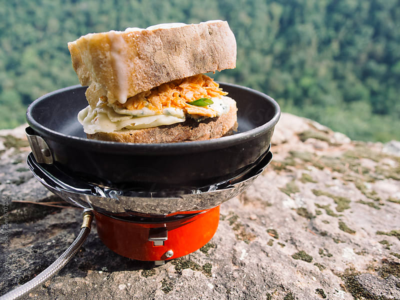 Buffalo chicken sandwich made on a cliff while camping by Jeremy Pawlowski for Stocksy United