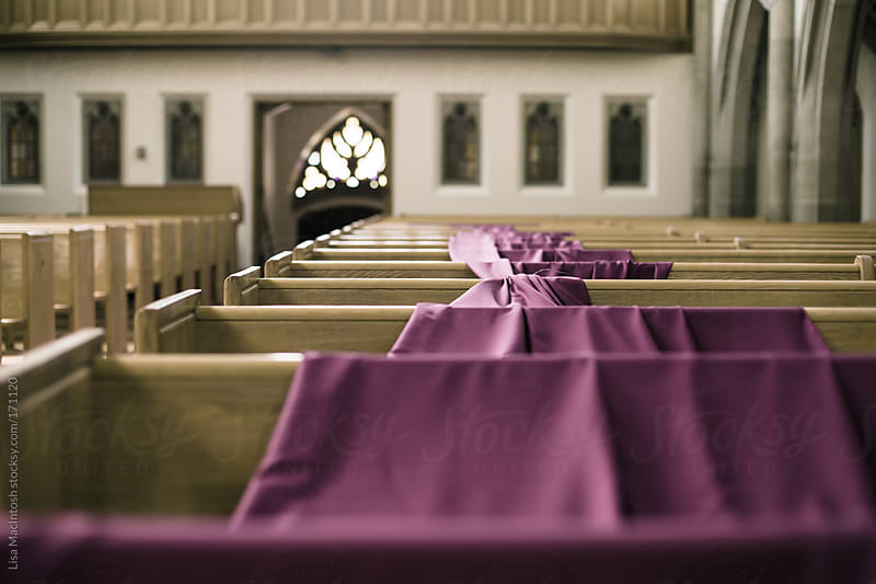 purple linen draped across numerous church pews in old church by Lisa MacIntosh for Stocksy United