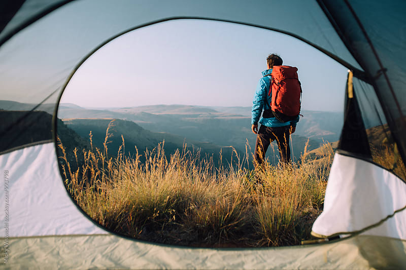 hiker standing outside his summit camp tent overlooking a scenic valley by Micky Wiswedel for Stocksy United