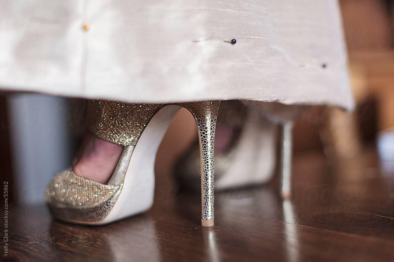 A women's feet in sexy, gold shoes peak out from the hemline of a gold dress that is pinned up. by Holly Clark for Stocksy United