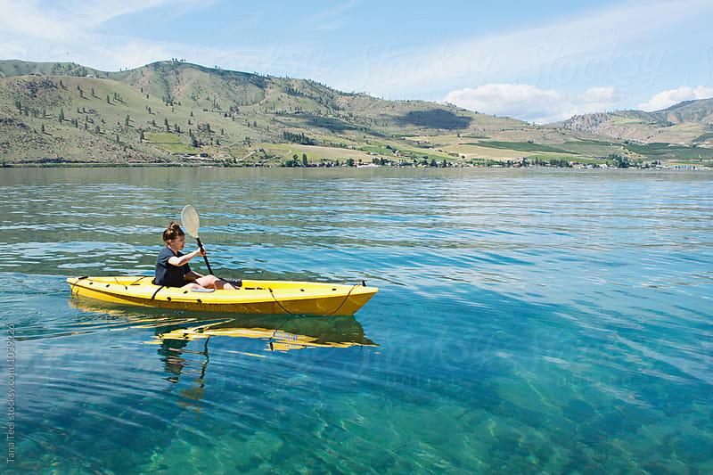 teenager paddle kayak in lake by Tana Teel for Stocksy United