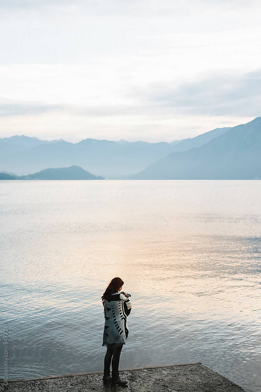 Woman relaxing in the nature across the lake by Simone Becchetti for Stocksy United