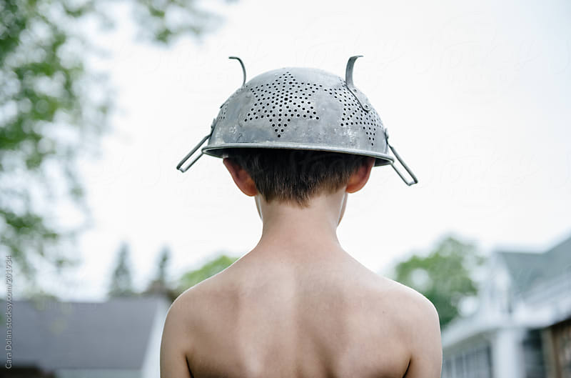 Boy plays outside in his backyard wearing a colander as a space helmet by Cara Dolan for Stocksy United