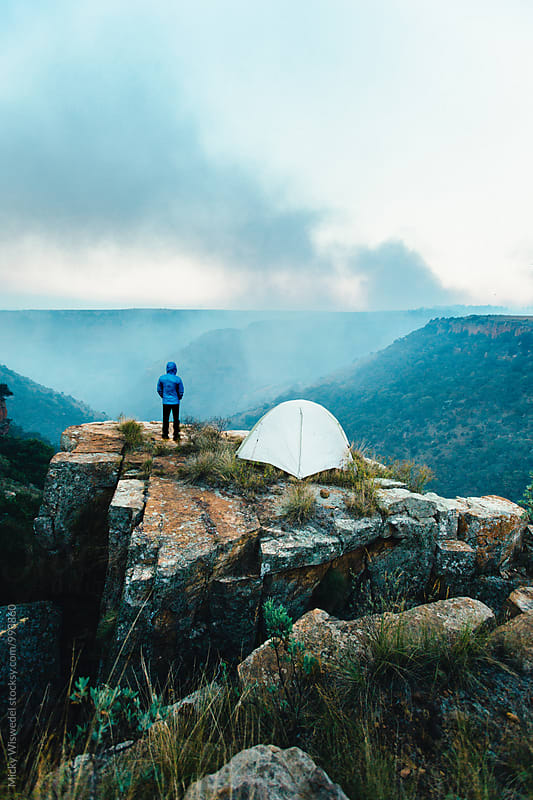Hiker and tent on a rocky outcrop in a remote valley by Micky Wiswedel for Stocksy United