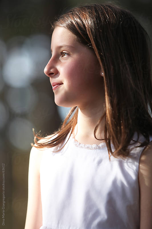 Side profile of young  girl wearing white dress in bright outdoor sunlight  by Dina Giangregorio for Stocksy United