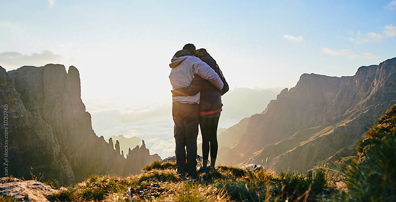 Young hiking couple holding each other while enjoying the sunrise over an epic mountainous valley.  by Jacques van Zyl for Stocksy United