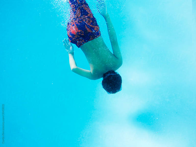 Young swimmer swimming towards the bottom of pool by Curtis Kim for Stocksy United