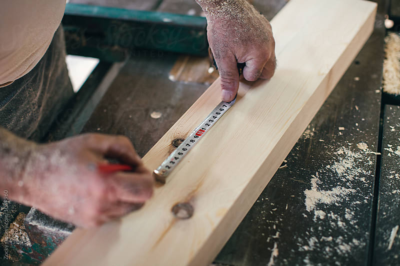 A close up of a carpenters hands measuring a piece of wood using a tapeline and a pencil by Zocky for Stocksy United