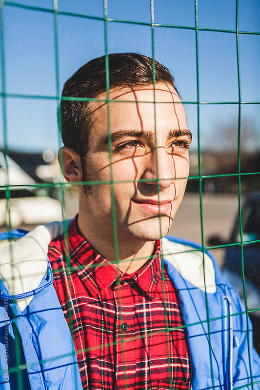 Portrait of a Young Man against a Net by Giorgio Magini for Stocksy United