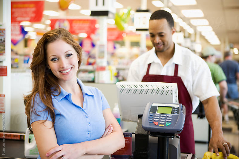 Supermarket: Cheerful Woman At Checkout Counter by Sean Locke for Stocksy United
