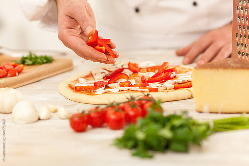 Chef preparing a pizza.  by Mosuno for Stocksy United