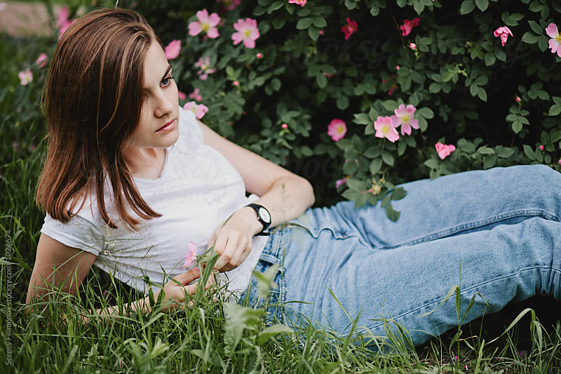 Young model beautiful girl lying on the grass in a lush garden by Sergey Filimonov for Stocksy United