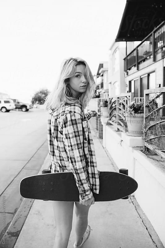 Blonde girl walking down sidewalk holding skateboard by Curtis Kim for Stocksy United