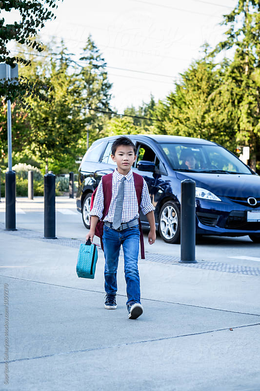 Back to school: Asian kid walking in school after dropped off by his mother by Suprijono Suharjoto for Stocksy United
