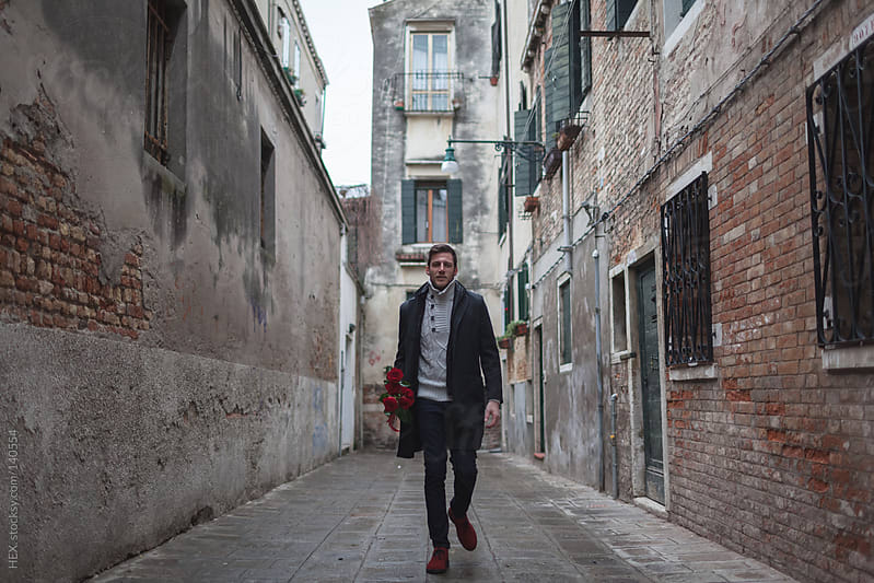 Man Walking With Red Roses Bouquet in Venice by HEX. for Stocksy United