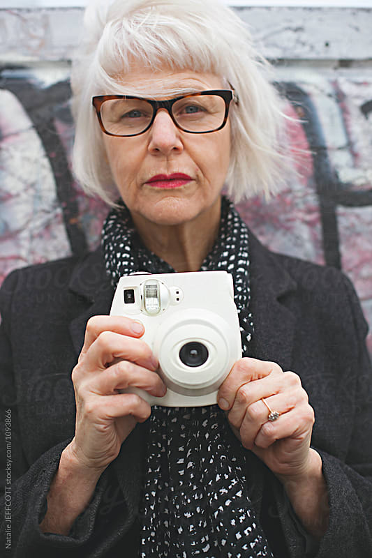 Older mature female / woamn using a camera outdoors in front of painted wall by Natalie JEFFCOTT for Stocksy United