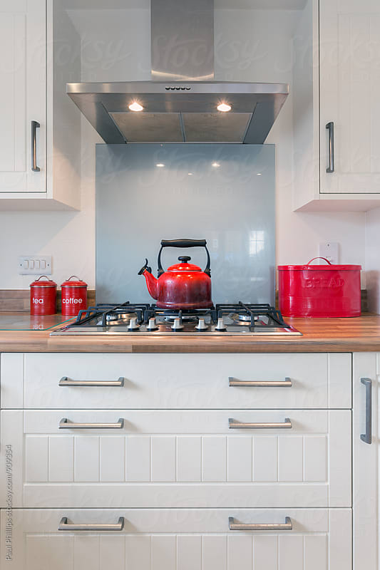 Red kettle and accessories in a contemporary kitchen. by Paul Phillips for Stocksy United