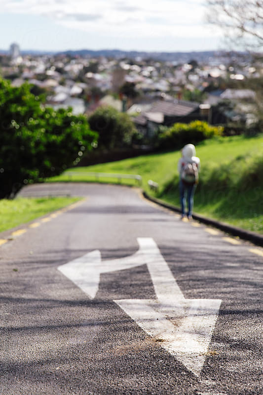 Woman walking on a sloping road by Andrey Pavlov for Stocksy United