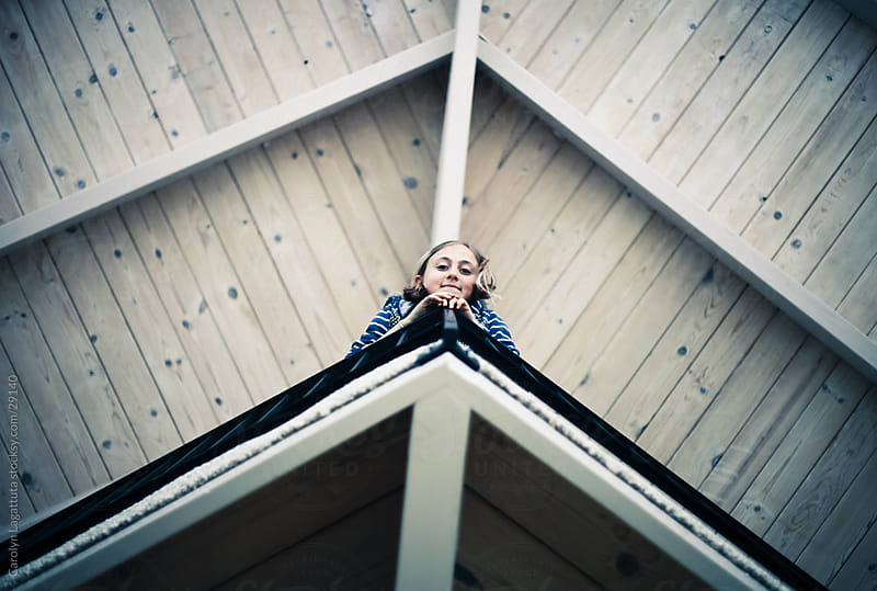 Little girl looking over a balcony smiling by Carolyn Lagattuta for Stocksy United
