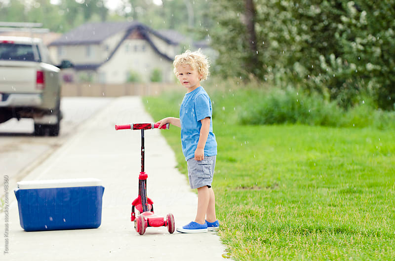 young boy with scooter by Tomas Kraus for Stocksy United